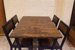 Δρύινος να δειπνήσει πίνακας με τις καρέκλες στο σκοτεινό δωμάτιο Στοκ Φωτογραφία