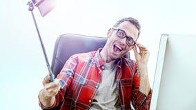 Δυναμικός επιχειρηματίας διασκέδασης στον υπολογιστή του που παίρνει ένα εύθυμο selfie Στοκ Φωτογραφία