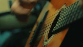 Δυναμικός στενός επάνω πυροβολισμός της όμορφης κιθάρας παιχνιδιού ατόμων φιλμ μικρού μήκους