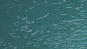 Δυνατή βροχή στο πυροβολισμό νερού Πτώση σταγόνων βροχής στο νερό σε σε αργή κίνηση φιλμ μικρού μήκους