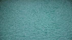 Δυνατή βροχή στο πυροβολισμό νερού Πτώση σταγόνων βροχής στο νερό σε σε αργή κίνηση απόθεμα βίντεο