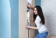 Δυσαρεστημένο κορίτσι που προσπαθεί να κλείσει την πλήρη ντουλάπα Στοκ Φωτογραφία