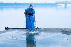 Δυσνόητο άτομο στο μπλε καταβρέχοντας νερό κιμονό με το ξύλινο ραβδί στοκ φωτογραφία με δικαίωμα ελεύθερης χρήσης