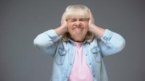 Δυστυχισμένα ηλικίας κλείνοντας αυτιά γυναικών, που υφίστανται τον ισχυρό πονοκέφαλο, θορυβώδεις γείτονες απόθεμα βίντεο