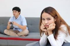 Δυστυχισμένηη ασιατική γυναίκα μετά από να υποστηρίξει με το φίλο στο καθιστικό Κακή έννοια ζευγών σχέσης στοκ εικόνες