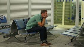 Δυστυχισμένη αρσενική συνεδρίαση επιβατών στη αίθουσα αναμονής, πτήση που ακυρώνεται ή καθυστερημένη φιλμ μικρού μήκους