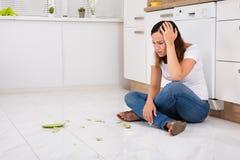 Δυστυχισμένη γυναίκα που εξετάζει το σπασμένο πιάτο στο πάτωμα Στοκ φωτογραφία με δικαίωμα ελεύθερης χρήσης