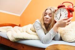 Δυστυχισμένη γυναίκα που ξυπνά με το ξυπνητήρι Στοκ Φωτογραφία