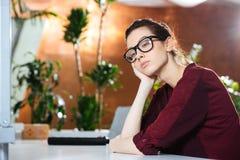 Δυστυχισμένη επιχειρησιακή γυναίκα στα γυαλιά που κάθεται στο γραφείο Στοκ Εικόνες