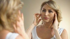 Δυστυχισμένη ηλικίας γυναίκα που κοιτάζει στον καθρέφτη στο σπίτι, σχετικά με το πρόσωπό της, διαδικασία γήρανσης απόθεμα βίντεο