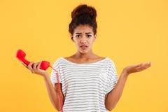 Δυστυχισμένη κυρία Displeased που κρατά το κόκκινο μικροτηλέφωνο στεμένος που απομονώνεται Στοκ φωτογραφία με δικαίωμα ελεύθερης χρήσης