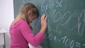 Δυστυχισμένη μαθήτρια κοντά στον πίνακα με τα παραδείγματα στα μαθηματικά στην κατηγορία δημοτικών σχολείων απόθεμα βίντεο