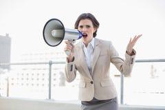 Δυστυχισμένη μοντέρνη καφετιά μαλλιαρή επιχειρηματίας που κραυγάζει megaphone Στοκ Φωτογραφίες