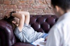 Δυστυχισμένη νέα γυναίκα σε μια υποδοχή συμβούλων ψυχολόγων στοκ εικόνα