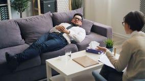 Δυστυχισμένη ομιλία νεαρών άνδρων που βρίσκεται στον καναπέ στο γραφείο του ψυχολόγου στην κλινική απόθεμα βίντεο