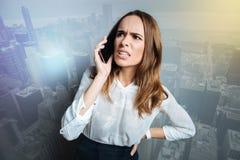 Δυστυχισμένη σκυθρωπή γυναίκα που μιλά στο τηλέφωνο Στοκ Εικόνες