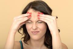 Δυστυχισμένη ταϊσμένη επάνω τονισμένη νέα γυναίκα με έναν επίπονο πονοκέφαλο στην αγωνία Στοκ Εικόνες