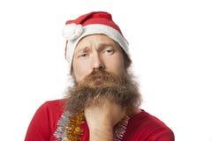 Δυστυχισμένος αστείος Άγιος Βασίλης με την πραγματική γενειάδα και το κόκκινο καπέλο και πουκάμισο που εξετάζει τη κάμερα με τη θ Στοκ Φωτογραφία