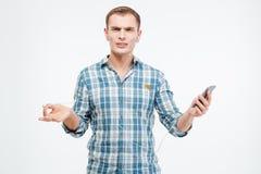 Δυστυχισμένος ενοχλημένος νεαρός άνδρας που ακούει τη μουσική από το smartphone Στοκ Εικόνα