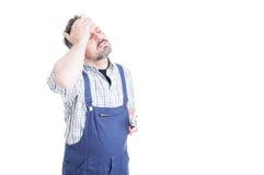 Δυστυχισμένος επισκευαστής με τις ιδιαίτερες προσοχές σχετικά με το μέτωπό του στοκ εικόνα