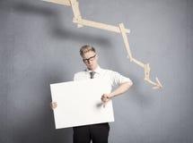 Δυστυχισμένος επιχειρηματίας που εμφανίζει επιτροπή μπροστά από την κατεβαίνοντας γραφική παράσταση. Στοκ εικόνα με δικαίωμα ελεύθερης χρήσης