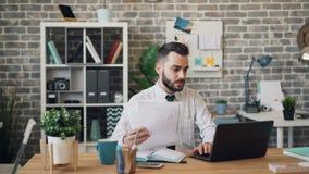 Δυστυχισμένος επιχειρηματίας που εξετάζει την οθόνη lap-top εγγράφων που φωνάζει ρίχνοντας τα έγγραφα φιλμ μικρού μήκους