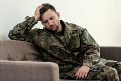 Δυστυχισμένος και λυπημένος στρατιώτης στο πράσινο moro ομοιόμορφο με το πολεμικό σύνδρομο στοκ εικόνα