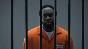 Δυστυχισμένος μαύρος φυλακισμένος που παρουσιάζει χειροπέδες, αθώο αρσενικό που περιμένουν τη δικαιοσύνη απόθεμα βίντεο