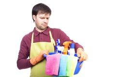 Δυστυχισμένος νεαρός άνδρας με την ποδιά και τον καθαρίζοντας εξοπλισμό Στοκ εικόνα με δικαίωμα ελεύθερης χρήσης