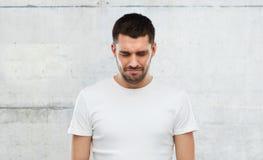 Δυστυχισμένος νεαρός άνδρας πέρα από το γκρίζο υπόβαθρο τοίχων Στοκ εικόνα με δικαίωμα ελεύθερης χρήσης