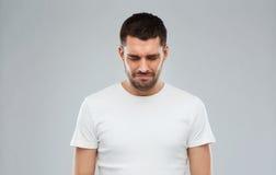 Δυστυχισμένος νεαρός άνδρας πέρα από το γκρίζο υπόβαθρο Στοκ φωτογραφία με δικαίωμα ελεύθερης χρήσης