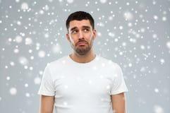 Δυστυχισμένος νεαρός άνδρας πέρα από το υπόβαθρο χιονιού Στοκ Εικόνες