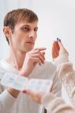Δυστυχισμένος νεαρός άνδρας που παίρνει ένα χάπι Στοκ Εικόνες
