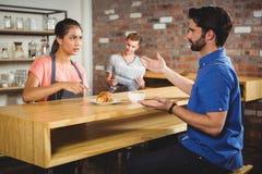 Δυστυχισμένος πελάτης που παραπονιέται για το croissant Στοκ Εικόνες