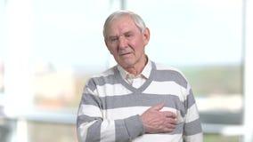 Δυστυχισμένος πρεσβύτερος που τρίβει το στήθος του απόθεμα βίντεο