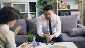 Δυστυχισμένος τονισμένος τύπος επιχειρηματίας που μιλά με τον ψυχολόγο στην αρχή απόθεμα βίντεο