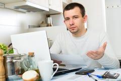 Δυστυχισμένος τύπος με το σημειωματάριο στην κουζίνα Στοκ εικόνα με δικαίωμα ελεύθερης χρήσης