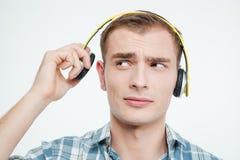 Δυστυχισμένος όμορφος νεαρός άνδρας που βγάζει τα ακουστικά Στοκ φωτογραφίες με δικαίωμα ελεύθερης χρήσης