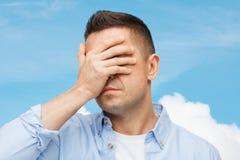 Δυστυχισμένο άτομο που καλύπτει τα μάτια του με το χέρι στοκ εικόνα