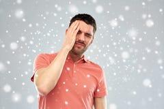 Δυστυχισμένο άτομο που πάσχει από τον επικεφαλής πόνο πέρα από το χιόνι στοκ φωτογραφίες