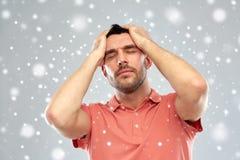 Δυστυχισμένο άτομο που πάσχει από τον επικεφαλής πόνο πέρα από το χιόνι στοκ εικόνες