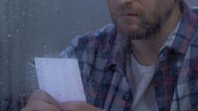 Δυστυχισμένο μέσης ηλικίας άτομο που εξετάζει την οικογενειακή φωτογραφία, που υφίσταται την αποσύνθεση, διαζύγιο φιλμ μικρού μήκους