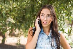 Δυστυχισμένο μικτό θηλυκό εφήβων φυλών που μιλά στο τηλέφωνο κυττάρων έξω στοκ φωτογραφία με δικαίωμα ελεύθερης χρήσης