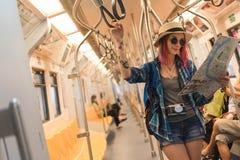Δυτικός ταξιδιώτης γυναικών με τα γυαλιά ηλίου που εξετάζει το χάρτη πόλεων στο τ Στοκ Εικόνες