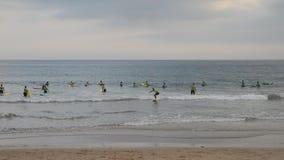 Δωδεκάδες της πρακτικής αρχαρίων που κάνει σερφ στα ψυχρά ατλαντικά νερά στην παραλία Carcavelos κοντά στη Λισσαβώνα φιλμ μικρού μήκους