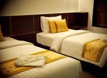 Δωμάτιο διπλών κρεβατιών με τα χρυσά καφετιά κίτρινα μαξιλάρια χρώματος Στοκ Εικόνες
