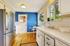 Δωμάτιο κουζινών με τα λευκά γραφεία, τους μπλε τοίχους και το γυαλί ικανούς Στοκ φωτογραφία με δικαίωμα ελεύθερης χρήσης
