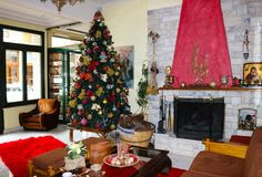 Δωμάτιο λόμπι-διαβίωσης ξενοδοχείων Botique στο χρόνο Χριστουγέννων με το δέντρο και την εστία στους Δελφούς Ελλάδα Στοκ Εικόνα