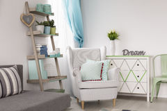 Δωμάτιο με τα δημιουργικούς ράφια, την πολυθρόνα και τον καναπέ στοκ φωτογραφίες με δικαίωμα ελεύθερης χρήσης