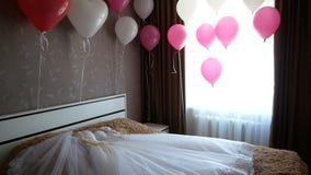 Δωμάτιο νυφών με τα ρόδινα και άσπρα μπαλόνια και φόρεμα στο κρεβάτι φιλμ μικρού μήκους